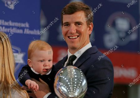 New York Giants NFL football quarterback Eli Manning holds his son Charles after announcing his retirement, in East Rutherford, N.J. Manning is among this year's inductees into the New Jersey Hall of Fame announced Wednesday, Aug. 5, 2020
