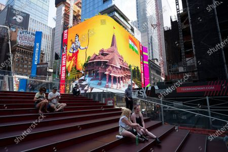 People take a break in Times Square as the imagery of the Hindu deity Ram and 3-D portraits of the proposed Hindu temple are displayed on a digital billboard, New York, to celebrate the groundbreaking ceremony of a temple dedicated to the Hindu god Ram by Indian Prime Minister Narendra Modi in Ayodhya, in New Delhi, India. Hindus rejoiced as Modi broke ground on a long-awaited temple of their most revered god, Ram, at the site of a demolished 16th century mosque