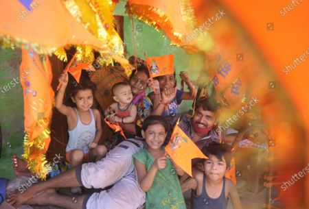 A family holds up flags with Lord Ram on it during festivities on the day of Bhumi Poojan of Ram Temple  on August 5, 2020 in Ayodhya, India. Prime Minister Narendra Modi said on Wednesday the construction of Ram temple will not only add to Ayodhya's grandeur but will also change the entire economy of the region after laying the foundation stone in accordance with the 'muhurat' or auspicious time.