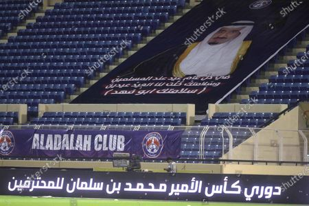 A poster depicting Saudi King Salman bin Abdulaziz Al Saud and felicitation messages after he underwent medical tests recently, is placed at the empty stadium before the start of the Saudi Professional League soccer match between Al-Adalah and Ettifaq, Al-Hasa, Saudi Arabia, 05 August 2020.
