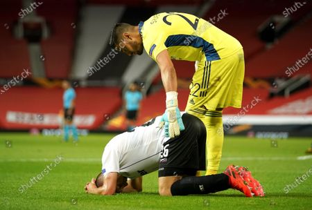 LASK's Reinhold Ranftl is consoled by Manchester United's goalkeeper Sergio Romero after the Europa League round of 16 second leg soccer match between Manchester United and LASK at Old Trafford in Manchester, England