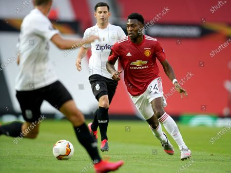 Manchester United's Timothy Fosu-Mensah, right, looks for support during the Europa League round of 16 second leg soccer match between Manchester United and LASK at Old Trafford in Manchester, England