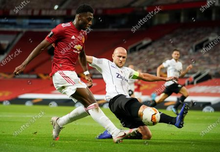 Manchester United's Timothy Fosu-Mensah, left, takes a shot at goal as LASK's Gernot Trauner, right, attempts to block the shot during the Europa League round of 16 second leg soccer match between Manchester United and LASK at Old Trafford in Manchester, England
