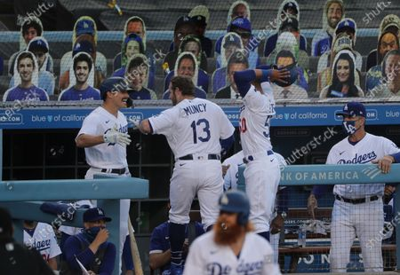 With cardboard cut-out fans in the background, Los Angeles Dodgers left fielder Enrique Hernandez (14),left, and Los Angeles Dodgers right fielder Mookie Betts (50), right, congratulate Los Angeles Dodgers second baseman Max Muncy (13) after he hit a solo homer off San Francisco Giants starting pitcher Tyler Anderson (31) in the first inning at Dodger Stadium on July 24, 2020 in Los Angeles, California. (Gina Ferazzi / Los Angeles Times)