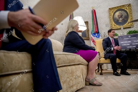 Arizona Gov. Doug Ducey, right, accompanied by his Deputy Chief of Staff Gretchen Conger, center, speaks during a meeting with President Donald Trump in the Oval Office of the White House in Washington