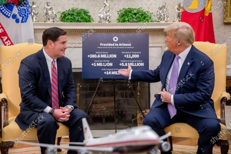 President Donald Trump gestures to a poster with coronavirus relief materials that have been provided to Arizona as he meets with Arizona Gov. Doug Ducey in the Oval Office of the White House in Washington