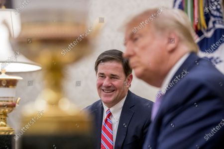 President Donald Trump meets with Arizona Gov. Doug Ducey, center, in the Oval Office of the White House in Washington