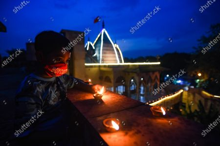 A boy lights earthen lamps to celebrate the foundation laying ceremony of the Ram temple in Ayodhya, at VHP Headquarters in Sankat Mochan Ashram, RK Puram  on August 5, 2020 in New Delhi, India. The grand celebrations for the bhoomi pujan started at 8 am and Prime Minister Narendra Modi performed the Ayodhya Ram Mandir bhoomi pujan at the auspicious time of 12:40 pm.