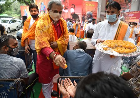 BJP Delhi Pradesh president Adesh Gupta distributing sweets at a viewing of a live telecast of the foundation laying ceremony in Ayodhya of the Ram Temple, at Valmiki Mandir on Mandir Marg  on August 5, 2020 in New Delhi, India. The grand celebrations for the bhoomi pujan started at 8 am and Prime Minister Narendra Modi performed the Ayodhya Ram Mandir bhoomi pujan at the auspicious time of 12:40 pm.