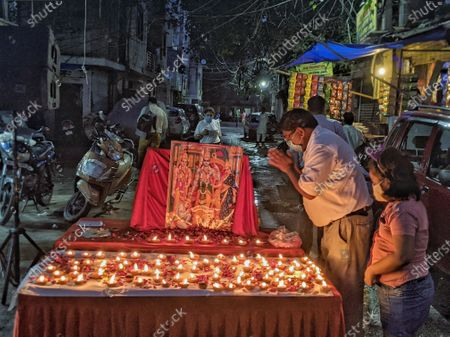 People praying at a podium that installed Lord Ram's photo in celebration of the Bhumi Pujan of Ayodhya's Ram Temple, at Bhogal on August 5, 2020 in New Delhi, India. The grand celebrations for the bhoomi pujan started at 8 am and Prime Minister Narendra Modi performed the Ayodhya Ram Mandir bhoomi pujan at the auspicious time of 12:40 pm.