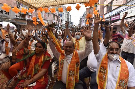People react while watching the live telecast of the Ram Temple foundation stone laying ceremony happening in Ayodhya, at Mulatani Dhanda at Paharganj on August 5, 2020 in New Delhi, India. The grand celebrations for the bhoomi pujan started at 8 am and Prime Minister Narendra Modi performed the Ayodhya Ram Mandir bhoomi pujan at the auspicious time of 12:40 pm.
