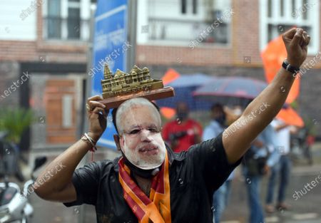 A man wearing a mask with Narendra Modi's image on it, holds a replica of the Ram Temple while celebrating on the occasion of the foundation stone laying ceremony for the construction of Ram Temple in Ayodhya, at Defence Enclave on August 5, 2020 in New Delhi, India. The grand celebrations for the bhoomi pujan started at 8 am and Prime Minister Narendra Modi performed the Ayodhya Ram Mandir bhoomi pujan at the auspicious time of 12:40 pm.