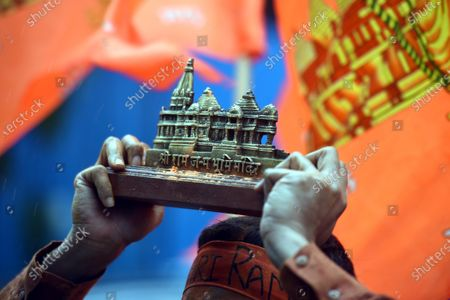 A man holds a replica of the Ram Temple while celebrating on the occasion of the foundation stone laying ceremony for the construction of Ram Temple in Ayodhya, at Defence Enclave on August 5, 2020 in New Delhi, India. The grand celebrations for the bhoomi pujan started at 8 am and Prime Minister Narendra Modi performed the Ayodhya Ram Mandir bhoomi pujan at the auspicious time of 12:40 pm.