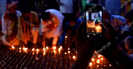 An individual takes a photo of people lighting earthen lamps at a Hanuman temple to celebrate the Bhumi Pujan ceremony of Ayodhya's Ram Temple on August 5, 2020 in Patna, India. The grand celebrations for the bhoomi pujan started at 8 am and Prime Minister Narendra Modi performed the Ayodhya Ram Mandir bhoomi pujan at the auspicious time of 12:40 pm.