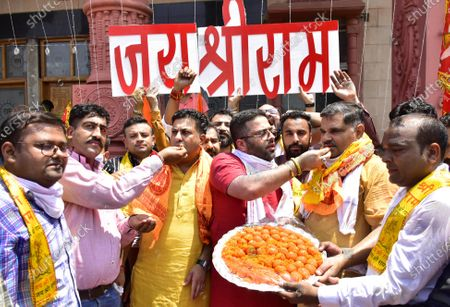 Activists of Bharatiya Janata Yuva Morcha (BJYM) eat sweets while celebrating the temple foundation laying ceremony happening in Ayodhya on August 5, 2020 in Amritsar, India. The grand celebrations for the bhoomi pujan started at 8 am and Prime Minister Narendra Modi performed the Ayodhya Ram Mandir bhoomi pujan at the auspicious time of 12:40 pm.