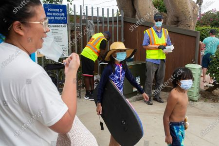 """From left: Michael Ward and Rob Howard and pass out surgical masks to beachgoers outside of Thousand Steps Beach on Sunday, Aug. 2, 2020 in Laguna Beach, CA. The City of Laguna Beach has re-employed former trolley drivers to act as """"mask ambassadors"""" for the summer, passing out masks and reminding people to wear them as they make their way to the beach. Though the mask ambassadors are associated with the Laguna Police Department, they are not handing out citations. (Gabriella Angotti-Jones / Los Angeles Times)"""