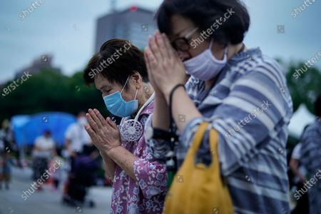 Women pray in front of a  cenotaph at Peace Memorial Park in Hiroshima, western Japan, early 06 August 2020.  On 06 August 2020 Japan marks the 75th anniversary of the bombing of Hiroshima. In 1945 the United States dropped two nuclear bombs over the cities of Hiroshima and Nagasaki on 06 and 09 August respectively, killing more than 200,000 people. This year's annual commemoration events were either canceled or scaled down amid the ongoing coronavirus pandemic.