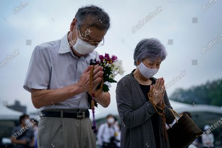 An elderly couple prays for victims in front of a cenotaph at Peace Memorial Park in Hiroshima, western Japan, early 06 August 2020.  On 06 August 2020 Japan marks the 75th anniversary of the bombing of Hiroshima. In 1945 the United States dropped two nuclear bombs over the cities of Hiroshima and Nagasaki on 06 and 09 August respectively, killing more than 200,000 people. This year's annual commemoration events were either canceled or scaled down amid the ongoing coronavirus pandemic.