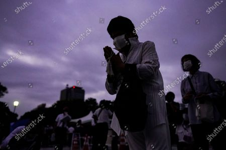 A woman prays for victims in front of a cenotaph at Peace Memorial Park in Hiroshima, western Japan, early 06 August 2020.  On 06 August 2020 Japan marks the 75th anniversary of the bombing of Hiroshima. In 1945 the United States dropped two nuclear bombs over the cities of Hiroshima and Nagasaki on 06 and 09 August respectively, killing more than 200,000 people. This year's annual commemoration events were either canceled or scaled down amid the ongoing coronavirus pandemic.