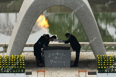 Kazumi Matsui, right, mayor of Hiroshima, and the family of the deceased bow before they place the victims list of the Atomic Bomb at Hiroshima Memorial Cenotaph during the ceremony to mark the 75th anniversary of the bombing at the Hiroshima Peace Memorial Park, in Hiroshima, western Japan