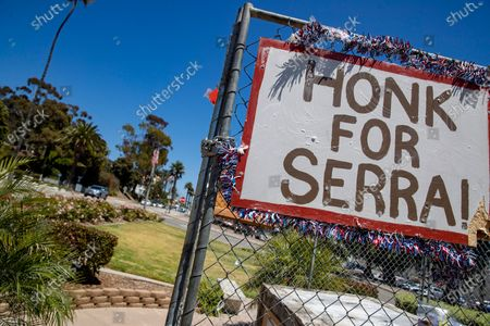 A sign urging passersby to honk in support of a statue of Fr. Juniper Serra which once stood at this spot in front of Ventura city hall on Saturday, Aug. 1, 2020 in Ventura, CA. (Brian van der Brug / Los Angeles Times)