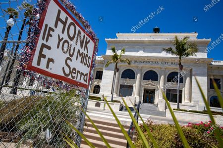 A sign urging passersby to honk if the miss a statue of Fr. Juniper Serra which once stood at this spot in front of Ventura city hall on Saturday, Aug. 1, 2020 in Ventura, CA. (Brian van der Brug / Los Angeles Times)