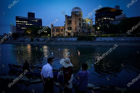 People watch as only a few lanterns float on the water of Motoyas River near the Peace Memorial Park in Hiroshima, western Japan, 06 August 2020. Only a handful of representatives released lanterns on the water after the annual floating lantern event which attracts thousands of people has been canceled this year to avoid the spreading of the coronavirus disease (COVID-19) pandemic. On 06 August 2020 Japan marks the 75th anniversary of the bombing of Hiroshima. In 1945 the United States dropped two nuclear bombs over the cities of Hiroshima and Nagasaki on 06 and 09 August respectively, killing more than 200,000 people. This year's commemoration events were either canceled or scaled down amid the ongoing coronavirus pandemic.