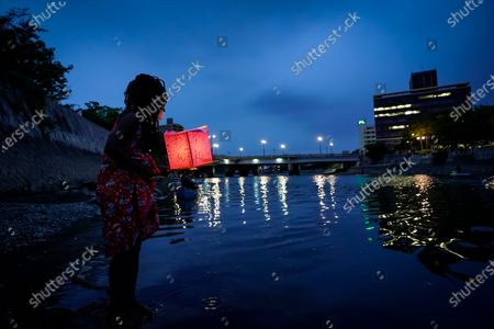 Seven-year-old Kenyan girl Joyce Makokha stands in the water as she placs a lantern on the water of Motoyasu River near the Peace Memorial Park in Hiroshima, western Japan, 06 August 2020. Only a handful of representatives released lanterns on the water after the annual floating lantern event which attracts thousands of people has been canceled this year to avoid the spreading of the coronavirus disease (COVID-19) pandemic. On 06 August 2020 Japan marks the 75th anniversary of the bombing of Hiroshima. In 1945 the United States dropped two nuclear bombs over the cities of Hiroshima and Nagasaki on 06 and 09 August respectively, killing more than 200,000 people. This year's commemoration events were either canceled or scaled down amid the ongoing coronavirus pandemic.