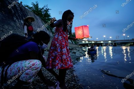 Seven-year-old Kenyan girl Joyce Makokha (R) is helped by her mother Grace as she places lantern on the water of Motoyasu River near the Peace Memorial Park in Hiroshima, western Japan, 06 August 2020. Only a handful of representatives released lanterns on the water after the annual floating lantern event which attracts thousands of people has been canceled this year to avoid the spreading of the coronavirus disease (COVID-19) pandemic. On 06 August 2020 Japan marks the 75th anniversary of the bombing of Hiroshima. In 1945 the United States dropped two nuclear bombs over the cities of Hiroshima and Nagasaki on 06 and 09 August respectively, killing more than 200,000 people. This year's commemoration events were either canceled or scaled down amid the ongoing coronavirus pandemic.