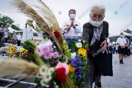An elderly woman offers a flower before praying for the victims in front of a cenotaph at Peace Memorial Park in Hiroshima, western Japan, early 06 August 2020. On 06 August 2020, Japan marks the 75th anniversary of the bombing of Hiroshima. In 1945 the United States dropped two nuclear bombs over the cities of Hiroshima and Nagasaki on 06 and 09 August respectively, killing more than 200,000 people. This year's annual commemoration events were either canceled or scaled down amid the ongoing coronavirus pandemic.