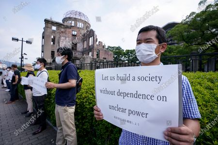 An anti-nuclear power demonstrator holds a placard in front of the Atomic Bomb Dome (L) at Peace Memorial Park in Hiroshima, western Japan, early 06 August 2020. On 06 August 2020, Japan marks the 75th anniversary of the bombing of Hiroshima. In 1945 the United States dropped two nuclear bombs over the cities of Hiroshima and Nagasaki on 06 and 09 August respectively, killing more than 200,000 people. This year's annual commemoration events were either canceled or scaled down amid the ongoing coronavirus pandemic.