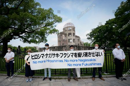 Anti-nuclear power demonstrators hold a banner in front of the Atomic Bomb Dome at Peace Memorial Park in Hiroshima, western Japan, early 06 August 2020. On 06 August 2020, Japan marks the 75th anniversary of the bombing of Hiroshima. In 1945 the United States dropped two nuclear bombs over the cities of Hiroshima and Nagasaki on 06 and 09 August respectively, killing more than 200,000 people. This year's annual commemoration events were either canceled or scaled down amid the ongoing coronavirus pandemic.