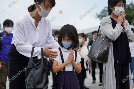 A young girl is accompanied by her mother as she prays in front of a cenotaph at Peace Memorial Park in Hiroshima, western Japan, early 06 August 2020. On 06 August 2020, Japan marks the 75th anniversary of the bombing of Hiroshima. In 1945 the United States dropped two nuclear bombs over the cities of Hiroshima and Nagasaki on 06 and 09 August respectively, killing more than 200,000 people. This year's annual commemoration events were either canceled or scaled down amid the ongoing coronavirus pandemic.