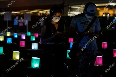 People stand among lanterns sitting on the ground during an 'online' lantern event where people gathered to watch virtual lanterns on large screens, in Hiroshima, Japan, 06 August 2020. The annual floating lantern event, which attracts thousands of people, has been canceled this year to avoid large gatherings. On 06 August 2020 Japan marks the 75th anniversary of the bombing of Hiroshima. In 1945 the United States dropped two nuclear bombs over the cities of Hiroshima and Nagasaki on 06 and 09 August respectively, killing more than 200,000 people. This year's annual commemoration events were either canceled or scaled down amid the ongoing coronavirus pandemic.