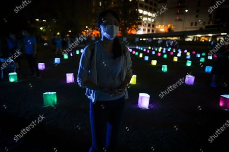 A woman stands among lanterns sitting on the ground during an 'online' lantern event where people gathered to watch virtual lanterns on large screens, in Hiroshima, Japan, 06 August 2020. The annual floating lantern event, which attracts thousands of people, has been canceled this year to avoid large gatherings. On 06 August 2020 Japan marks the 75th anniversary of the bombing of Hiroshima. In 1945 the United States dropped two nuclear bombs over the cities of Hiroshima and Nagasaki on 06 and 09 August respectively, killing more than 200,000 people. This year's annual commemoration events were either canceled or scaled down amid the ongoing coronavirus pandemic.