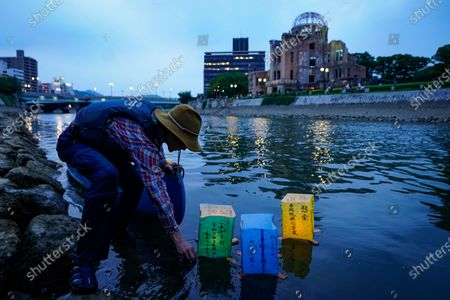 A volunteer releases lanterns on the water of Motoyasu River near the Peace Memorial Park in Hiroshima, western Japan, 06 August 2020. Only a handful of representatives released lanterns on the water after the annual floating lantern event which attracts thousands of people has been canceled this year to avoid the spreading of the coronavirus disease (COVID-19) pandemic. On 06 August 2020 Japan marks the 75th anniversary of the bombing of Hiroshima. In 1945 the United States dropped two nuclear bombs over the cities of Hiroshima and Nagasaki on 06 and 09 August respectively, killing more than 200,000 people. This year's commemoration events were either canceled or scaled down amid the ongoing coronavirus pandemic.