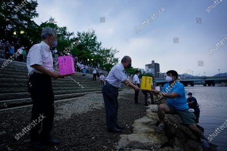 A man passes a lantern to a volunteer to release it on the water of Motoyasu River near the Peace Memorial Park in Hiroshima, western Japan, 06 August 2020. Only a handful of representatives released lanterns on the water after the annual floating lantern event which attracts thousands of people has been canceled this year to avoid the spreading of the coronavirus disease (COVID-19) pandemic. On 06 August 2020 Japan marks the 75th anniversary of the bombing of Hiroshima. In 1945 the United States dropped two nuclear bombs over the cities of Hiroshima and Nagasaki on 06 and 09 August respectively, killing more than 200,000 people. This year's commemoration events were either canceled or scaled down amid the ongoing coronavirus pandemic.