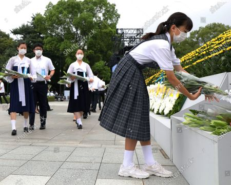 Young residents offer wreaths for victims of the 1945 atomic bombing during the memorial ceremony at the Peace Memorial Park in Hiroshima, western Japan, 06 August 2020. The ceremony was held to mark the 75th anniversary of the atomic bombing of Hiroshima in 1945.