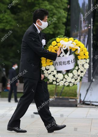 Japanese Prime Minister Shinzo Abe offers a wreath for victims of the 1945 atomic bombing during the memorial ceremony at the Peace Memorial Park in Hiroshima, western Japan, 06 August 2020. The ceremony was held to mark the 75th anniversary of the atomic bombing of Hiroshima in 1945.