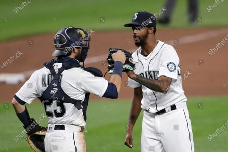 Stock Image of Seattle Mariners relief pitcher Carl Edwards Jr., right, shares congratulations with catcher Austin Nola after the Mariners defeated the Los Angeles Angels 7-6 in a baseball game, in Seattle