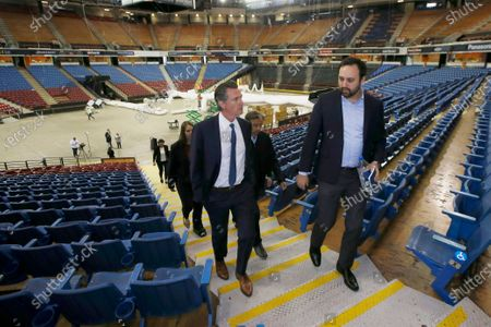 California Gov. Gavin Newsom, left, accompanied by Jason Kenney, deputy director of the Real Estate Services Division of the Department of General Services, tours Sleep Train Arena while it was being transformed into a 400-bed emergency field hospital in Sacramento, Calif. When California was anticipating a spring surge in coronavirus cases it turned an old NBA arena and practice facility into a field hospital prepared to take hundreds of patients. They were told to expect 30 to 60 patients within the first few days, but only nine arrived over the next 10 weeks