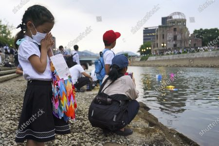 Saki Morioki, 5 years old, prays as paper lanterns float along the Motoyasu River in front of the Atomic Bomb Dome, . in Hiroshima, western Japan. Japan marked the 75th anniversary Thursday of the atomic bombing of Hiroshima. The official lantern event was cancelled to the public due to coronavirus but a small group of local representatives released some lanterns