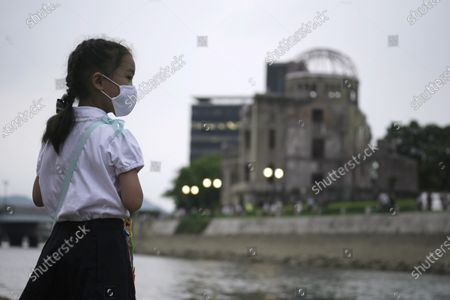 Saki Morioki, 5 years old, looks at paper lanterns floating along the Motoyasu River in front of the Atomic Bomb Dome, . in Hiroshima, western Japan. Japan marked the 75th anniversary Thursday of the atomic bombing of Hiroshima. The official lantern event was cancelled to the public due to coronavirus but a small group of local representatives released some lanterns