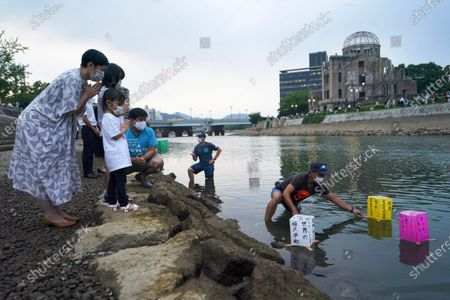 People pray as paper lanterns float along the Motoyasu River in front of the Atomic Bomb Dome, . in Hiroshima, western Japan. Japan marked the 75th anniversary Thursday of the atomic bombing of Hiroshima. The official lantern event was cancelled to the public due to coronavirus but a small group of local representatives released some lanterns