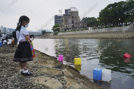 Saki Morioki, 5 years old, watches paper lanterns floating along the Motoyasu River in front of the Atomic Bomb Dome, . in Hiroshima, western Japan. Japan marked the 75th anniversary Thursday of the atomic bombing of Hiroshima. The official lantern event was cancelled to the public due to coronavirus but a small group of local representatives released some lanterns