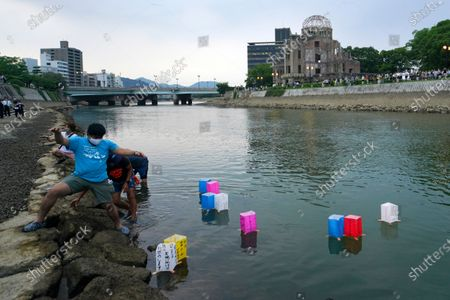 Volunteers release paper lanterns along the Motoyasu River in front of the Atomic Bomb Dome, . in Hiroshima, western Japan. Japan marked the 75th anniversary Thursday of the atomic bombing of Hiroshima. The official lantern event was cancelled to the public due to coronavirus but a small group of local representatives released some lanterns