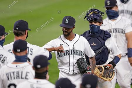 Stock Photo of Seattle Mariners relief pitcher Carl Edwards Jr., center, shares congratulations with manager Scott Servais as catcher Austin Nola follows after the team beat the Los Angeles Angels in a baseball game, in Seattle. The Mariners won 7-6