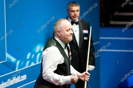 John Higgins celebrates after making a 147 at the Betfred World Championship for the first time. He becomes the seventh player to make a maximum break at the Crucible, and the first since 2012.