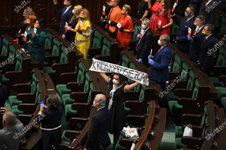 Opposition MP hold a banner 'Perjury' as other MPs wear outfits in rainbow colors during the swearing-in ceremony before the National Assembly of the Republic of Poland, a joint session of the Sejm (lower house) and Senate in Warsaw, Poland, 06 August 2020. President Andrzej Duda will start a second term after winning the presidential election held on 12 July, in which he defeated Rafal Trzaskowski, the candidate of the Civic Coalition.