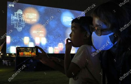 A boy and his mother view a projection of virtual paper lanterns floating in prayer for the victims of the 1945 atomic bombing in Hiroshima, western Japan, 06 August 2020. Japan marks on 06 August 2020 the 75th anniversary of the bombing of Hiroshima. In 1945 the United States dropped two nuclear bombs over the cities of Hiroshima and Nagasaki on 06 and 09 August respectively, killing more than 200,000 people. This year's commemoration events were either canceled or scaled down amid the ongoing coronavirus disease (COVID-19) pandemic.